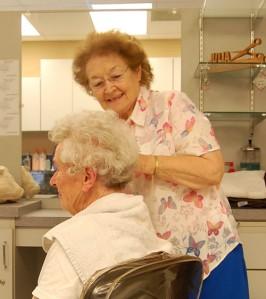 Sister Julia McGanty trims Dellora Guyer's hair.