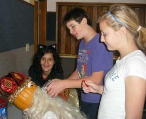 Pratum students decorate their scarecrow king scarecrow.