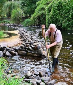 Mel Wildberger creates artwork using rocks in Silver Creek. Photo by Jim Kinghorn